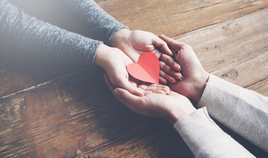 hands holding red paper heart