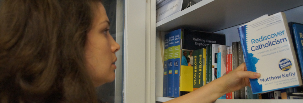 Female adult taking a book of a shelf